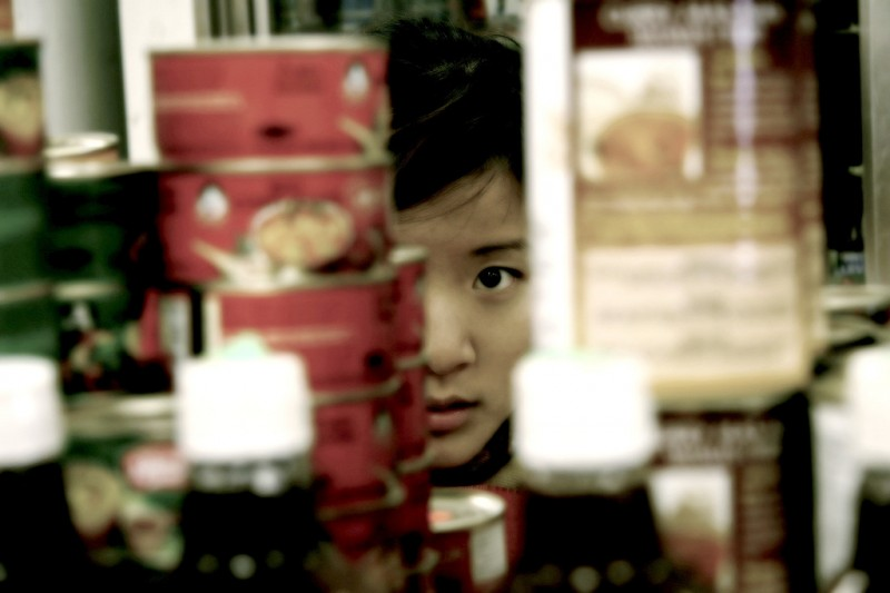 Woman peeking through objects on a shelf.