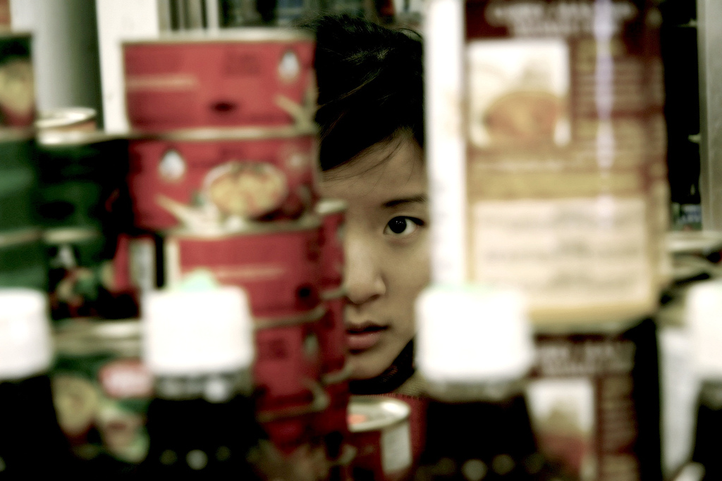 Woman peeking through objects on a shelf.